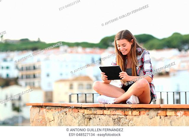 Happy teenage female watching media on tablet sitting on a ledge in a town