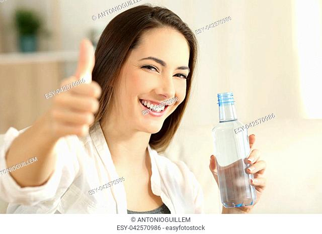 Portrait of a happy girl holding a water bottle gesturing thumbs up sitting on a couch in the living room at home