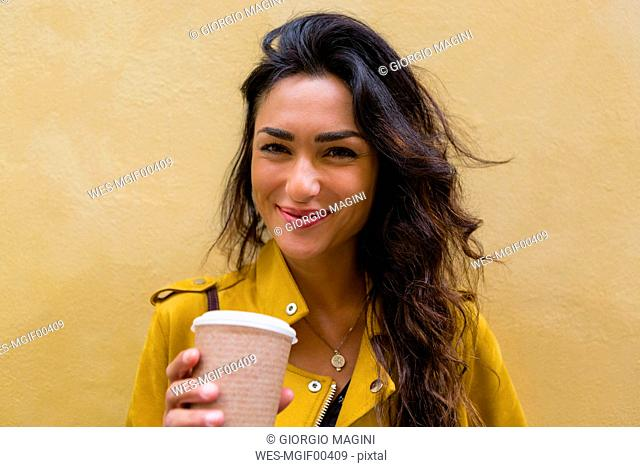 Portrait of young woman wearing yellow leather jacket, holding cup of coffee