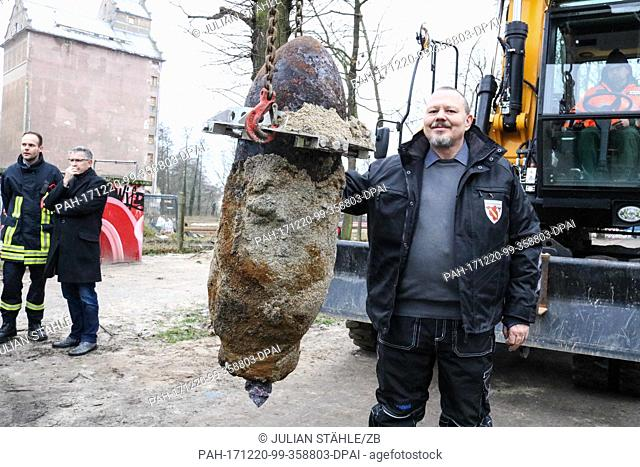 The demolition expert Andre Mueller (R) stands next to the defused aerial bomb that is held by a crane hook in Oranienburg, Germany, 20 December 2017