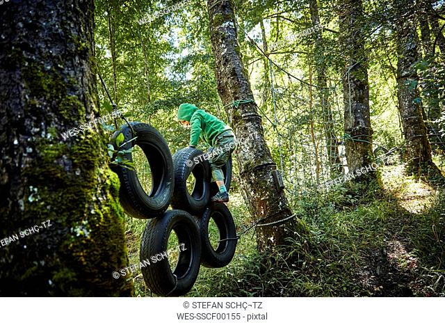 Boy balancing on tyres at an adventure park in forest