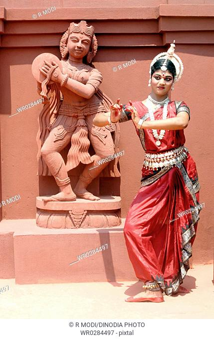 Woman performing classical traditional Odissi dance at statue on stage MR736C
