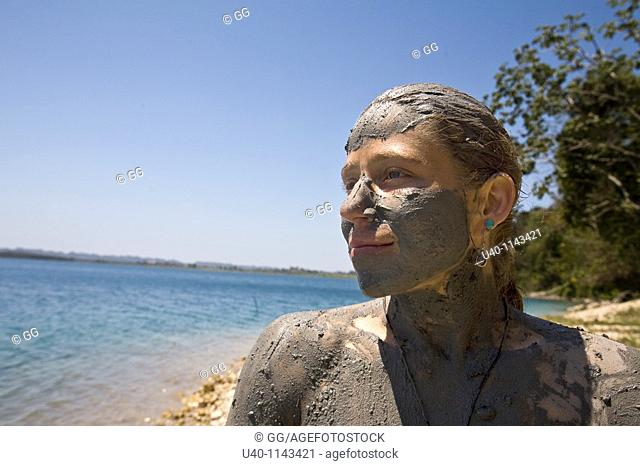 Guatemala, Peten, woman taking mud bath