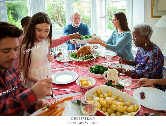 Multi-generation family eating at Christmas dinner table