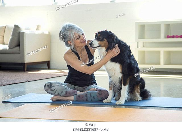 Woman on exercise mat petting dog