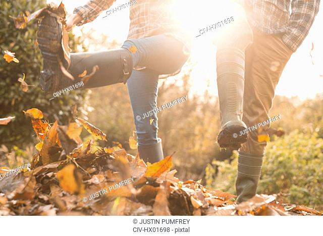 Couple in rain boots kicking autumn leaves