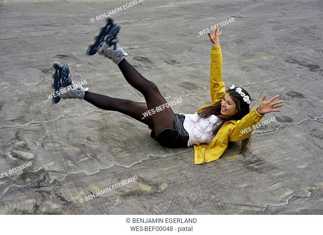 Smiling woman with inline skates falling on ground