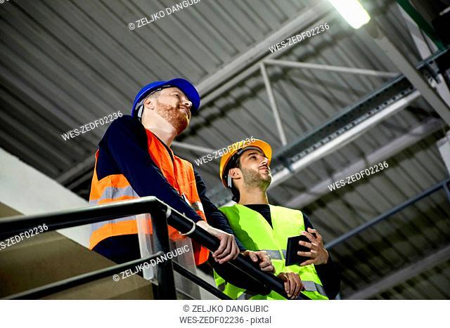 Two workers standing on upper floor in factory