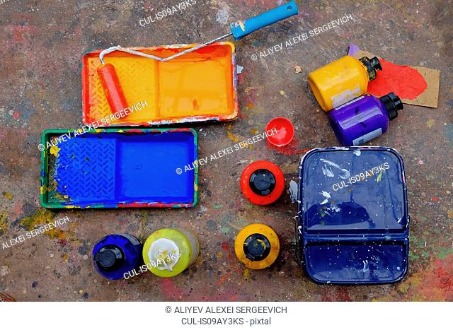 Overhead view of blue and yellow paint trays and paint roller