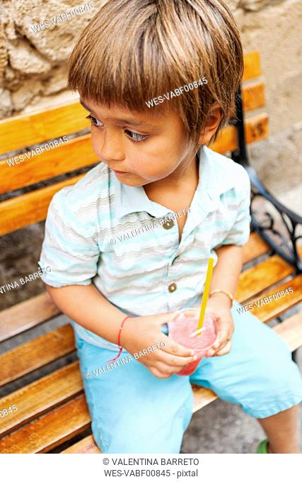 Little boy with cooled soft drink sitting on wooden bench