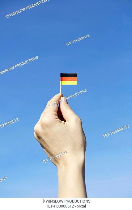 Woman holding German flag in hand