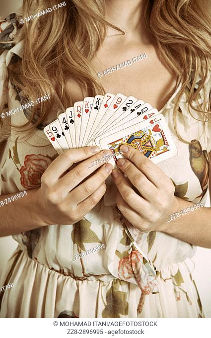 Close up of a woman holding playing cards