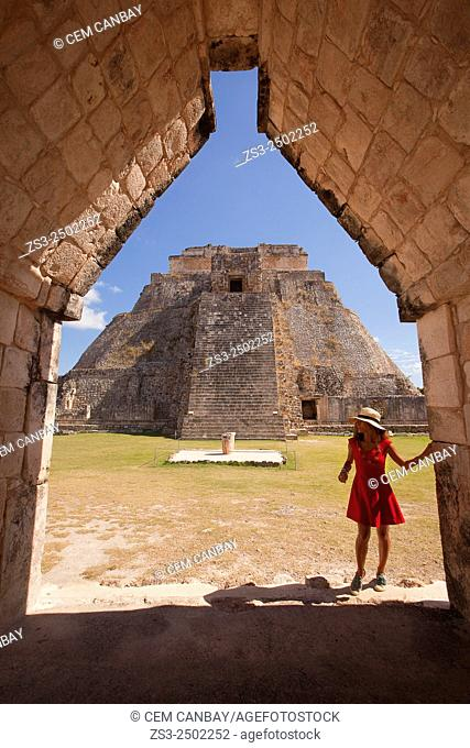 Tourist walking around the Pyramid of the Magician, Maya archeological site Uxmal, Yucatan, Mexico, Central America