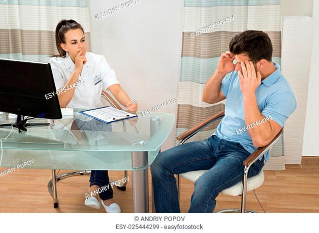 Young Female Doctor Looking At Male Patient Having Headache In Clinic