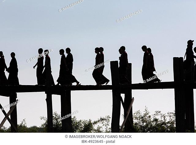 Silhouette of young Buddhist Novices on the U-Leg Bridge at Lake Taungthaman, Myanmar, Asia