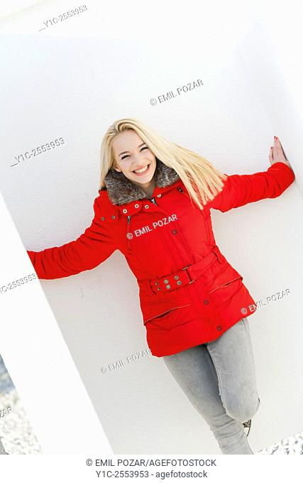 Blond teen girl in Red jacket spreading hands