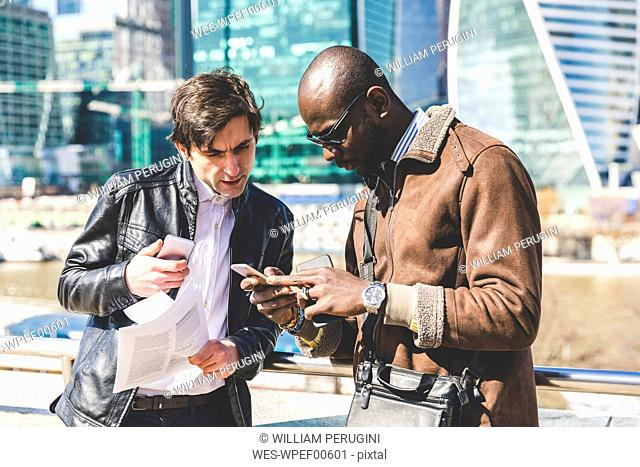Russia, Moscow, two businessmen in the city looking at cell phone