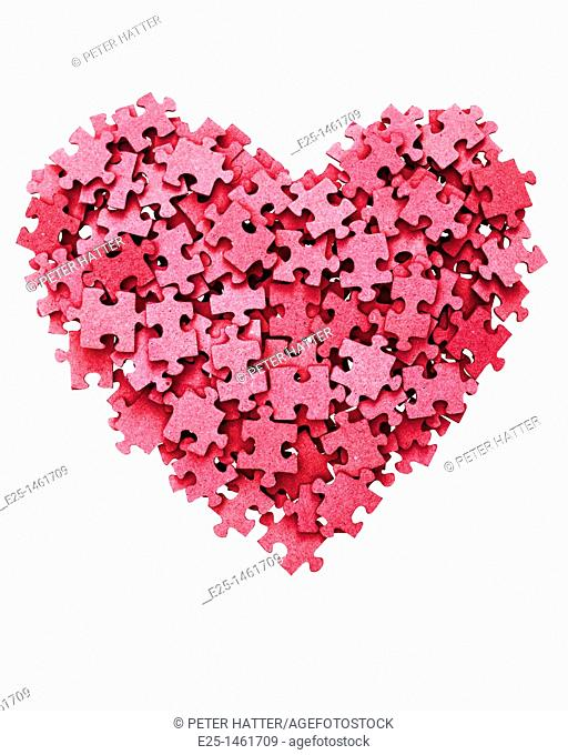 Heart shape symbol made from blank red jigsaw pieces isolated on a white background