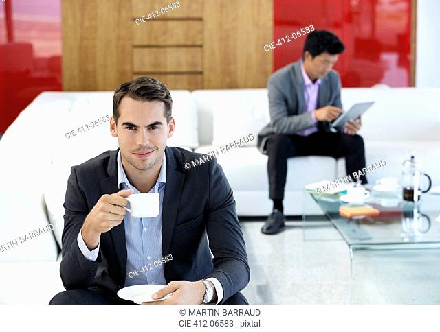 Businessman having cup of coffee in office
