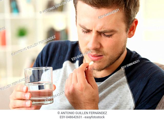 Man suffering taking a pill sitting on a sofa in the living room in a house interior
