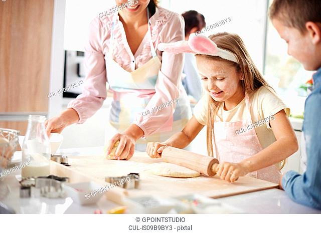 Girl with mother and brother easter baking at kitchen counter