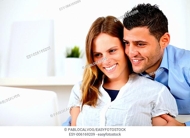 Portrait of a romantic young couple sitting on sofa at home looking to laptop screen