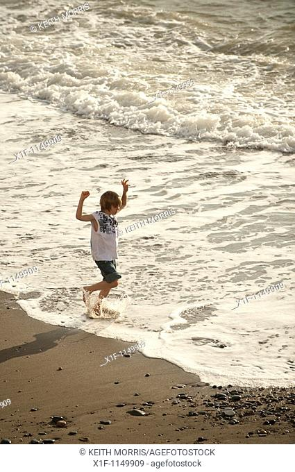 Young boy child running and splashing in the sea