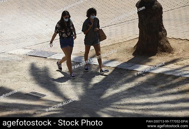 13 July 2020, Spain, Palma: Two young women wear mouth and nose protectors when walking through the old town. On Mallorca and the other Balearic Islands