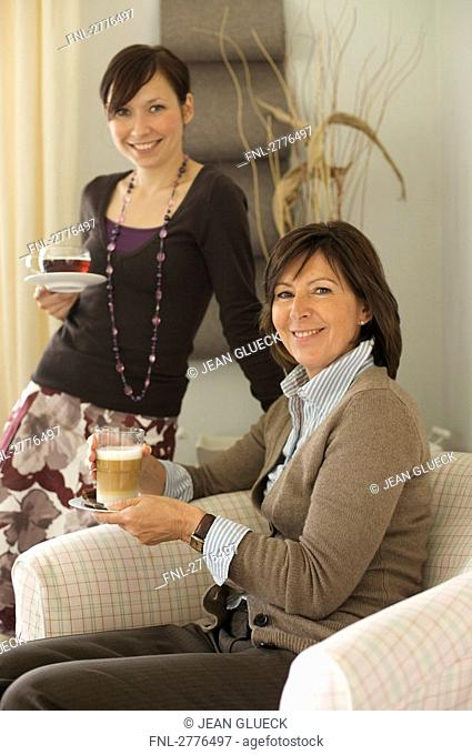 Portrait of woman and her daughter holding cups of coffee