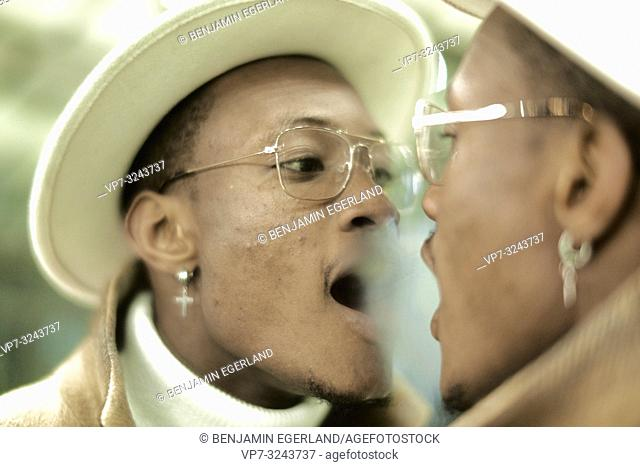 man breathing on mirror, looking at himself, self-perception, wearing Christian cross earring, faith, believe, in Munich, Germany