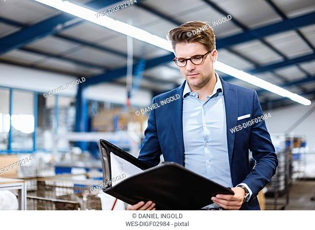 Portrait of a young manager in the shop floor, holding file