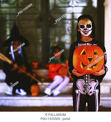 portrait of a child dressed up as a skeleton and holding a pumpkin on Halloween