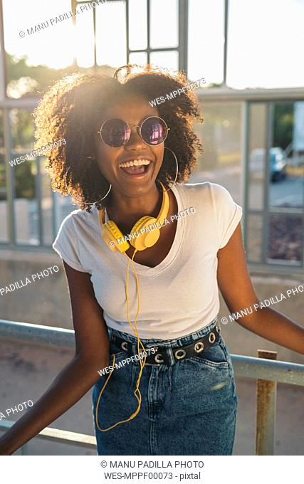 Portrait of laughing young woman with sunglasses and headphones