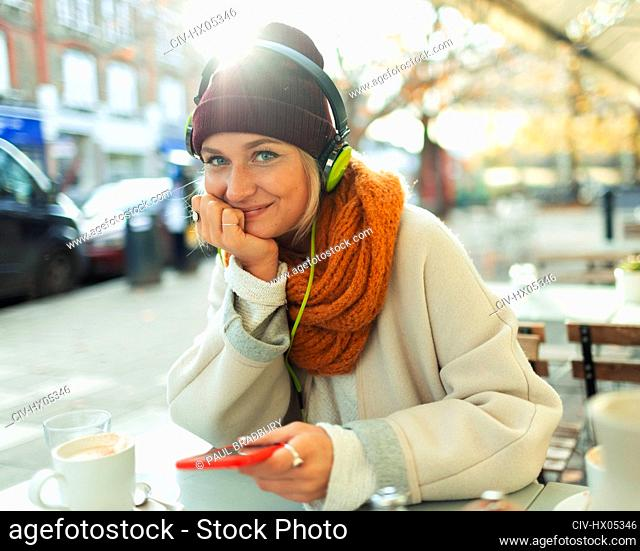 Portrait confident young woman listening to music with headphones and mp3 player at autumn sidewalk cafe