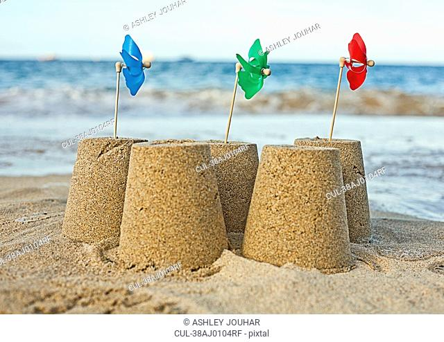 Sandcastles with pinwheels on beach