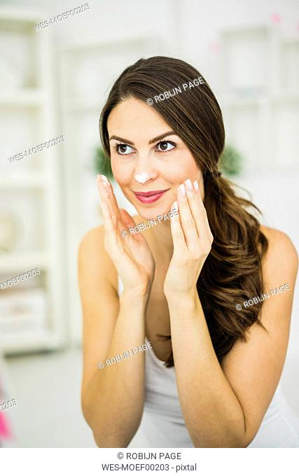 Portrait of smiling young woman creaming her face