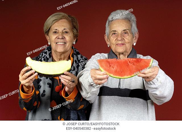 two senior women with fruit
