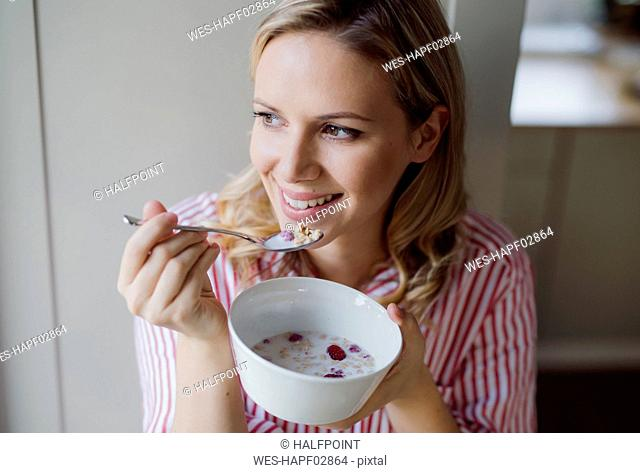 Smiling woman having breakfast in the morning at home