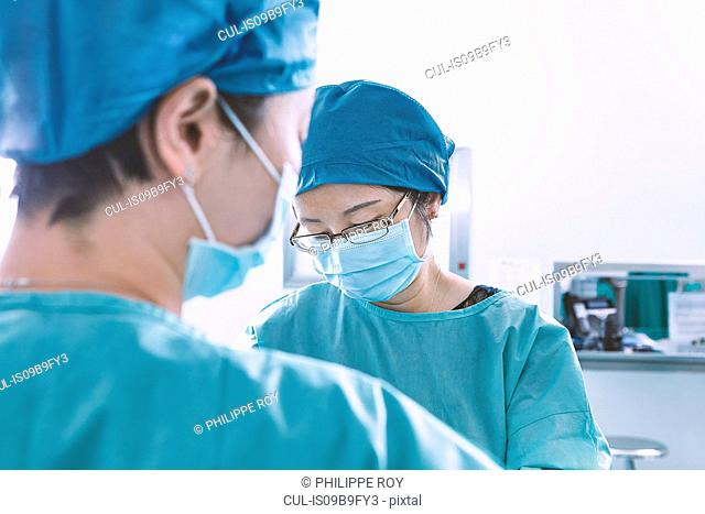 Over shoulder view of surgeon performing operation in maternity ward operating theatre