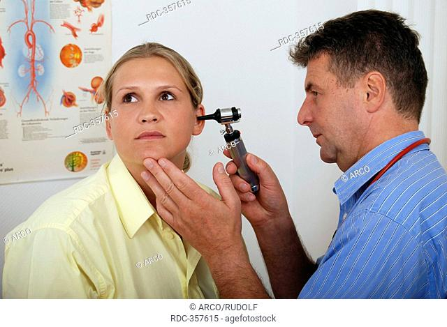 Woman under examination, checking ear