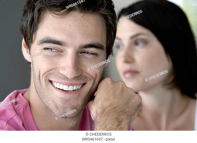 Close-up of a young man smiling with a young woman in the background