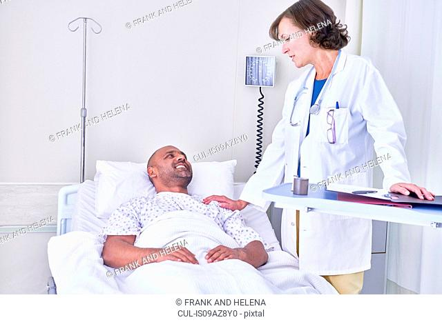 Doctor consulting with patient lying in hospital bed
