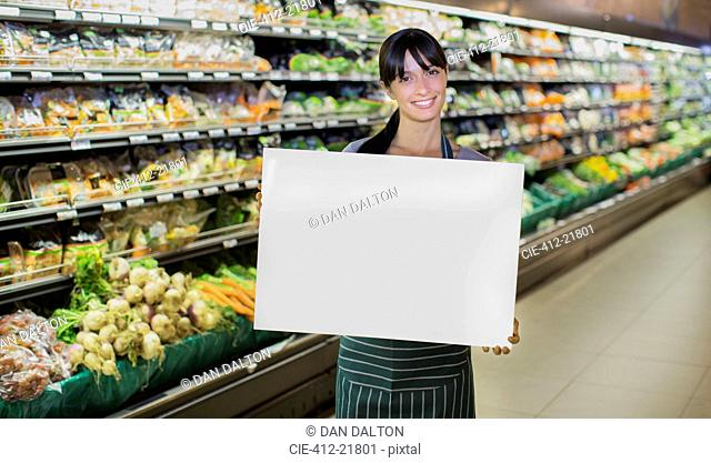 Clerk holding blank card in produce section of grocery store