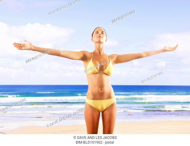 Mixed race woman wearing bikini on beach