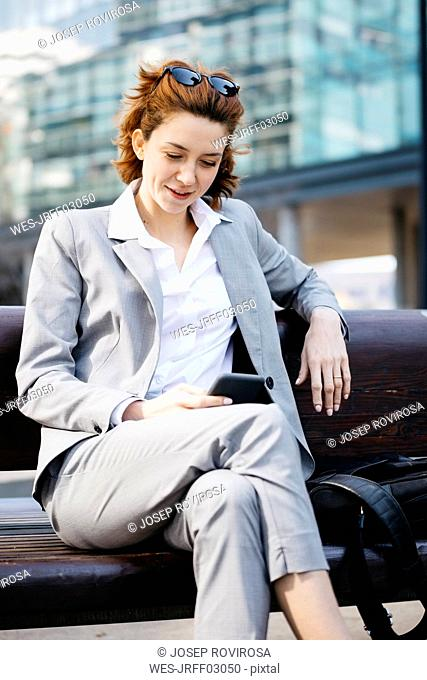 Young businesswoman sitting on a bench in the city, using smartphone