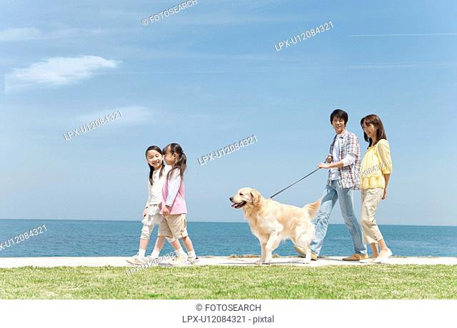 Family of Four and Dog Walking on Beach