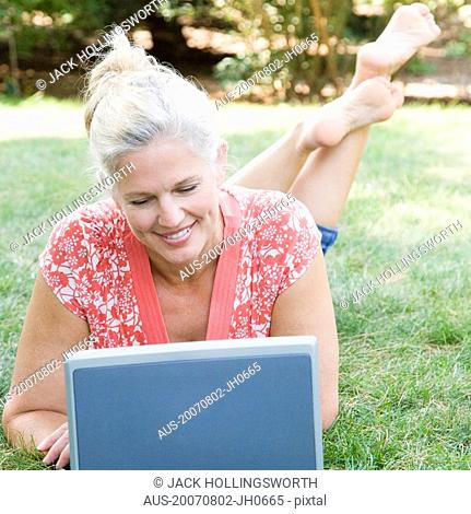 Mature woman lying in a park and using a laptop