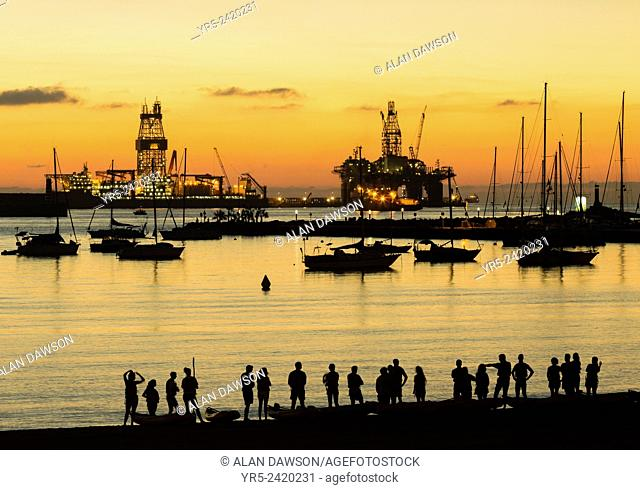 Canoists from University club at sunrise on Alcaravaneras beach in Las Palmas, Gran Canaria, Canary Islands, Spain. Drilling ship and rig undergoing repairs in...