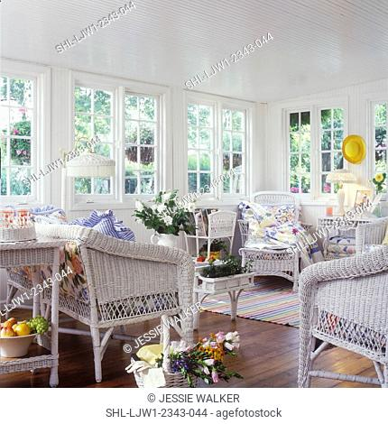 PORCH - white wicker with floral cushions, antique quilts. Cotton striped rug on wood floor, white lisianthus, yellow hat on wall, wicker lamp