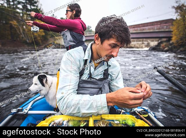 Fly-fisherman ties a fly onto a line while woman casts off boat